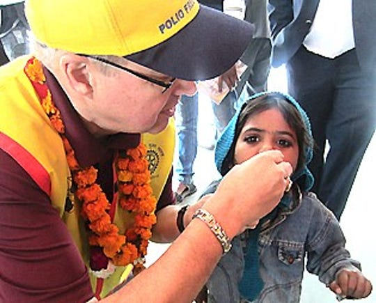 "Bill Tubbs gives polio vaccine, known as the ""Drops of Life,"" to a child during India's National Immunization Day in 2012."