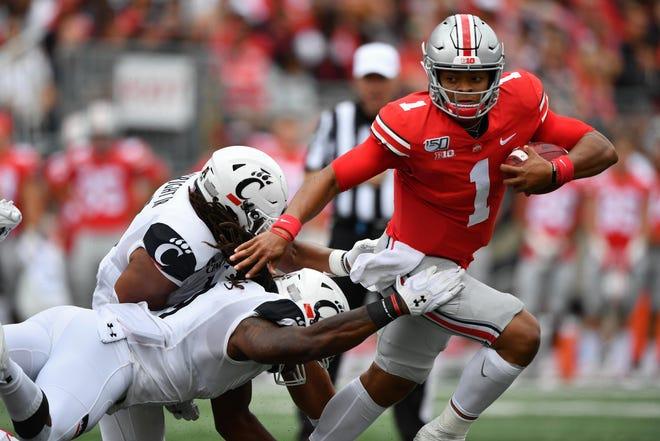 Ohio State quarterback Justin Fields eludes Cincinnati defenders at Ohio Stadium on Sept. 7, 2019 in Columbus, Ohio.
