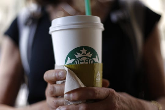 In this May 31, 2014 photo, a woman holds a coffee drink outside a Starbucks in downtown Chicago.  (AP Photo/Gene J. Puskar)