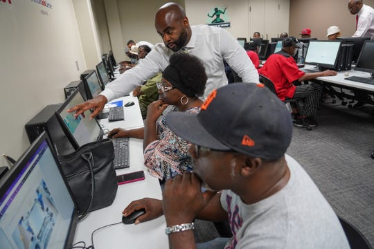 Jimmie Gladney helps Detroit residents logging in as they test and fill out an application for FCA jobs at the new Mack assembly plant at  the Northwest Activity Center in Detroit on Tuesday, Sept. 10, 2019.