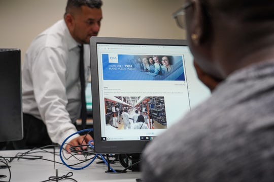 A Detroit resident watches a video while filling out an application for FCA jobs at the new Mack assembly plant at  the Northwest Activity Center in Detroit on Tuesday, Sept. 10, 2019.