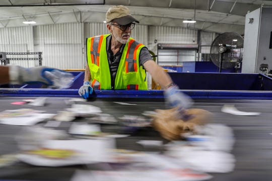 Detroit Free Press reporter Bill Laitner works the line sorting recycling as it whizzes by on a processing conveyor belt at SOCRRA material recovery facility in Troy in August. SOCRRA serves 12 municipalities in southeast Michigan.