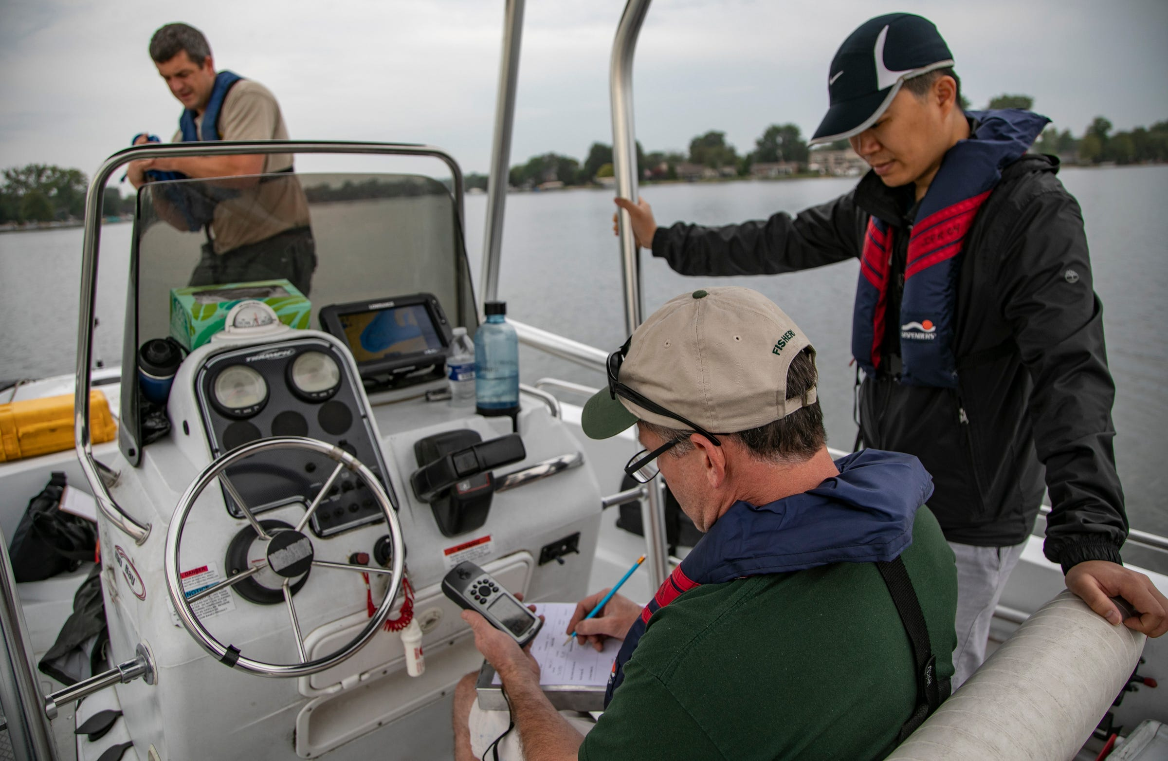 MDNR Resource Analyst Joe Nohner, left, prepares to anchor as Kevin Wehrly a fisheries research biologist with the MDNR's Institute for Fisheries Research marks their GPS coordinates on Cedar Island Lake in White Lake Township Tuesday, Sept. 10, 2019 as Research analyst from MSU Ken Yeh looks on.