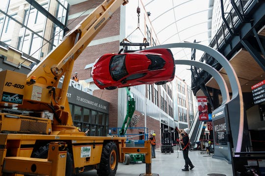 Workers install the 2020 Corvette Stingray on the wall at the northeast entrance of the Little Caesars Arena in downtown Detroit, Tuesday, September 10, 2019.
