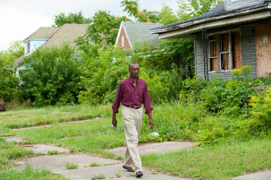 Oris Floyd, 71, who has lived on Tacoma Street near Gratiot Avenue in Detroit for more than two decades, walks past some of the 15 blighted and abandoned houses on his street on the city's east side.
