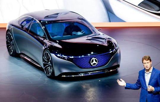 Ola Kaellenius, CEO of the car manufacturer Mercedes, stands next to a 'Vision EQS' car.