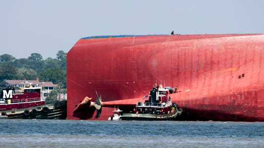 Rescuers work near the stern of the vessel Golden Ray as it lays on its side near the Moran tug boat Dorothy Moran in Jekyll Island, Ga.