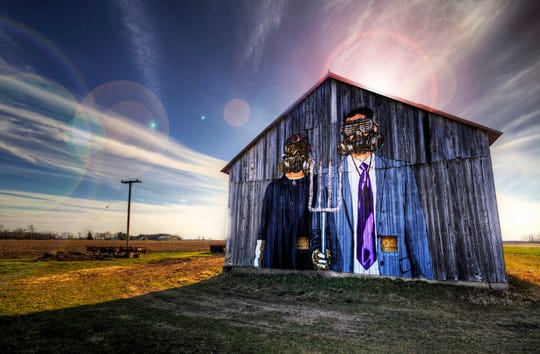 "Detroit's artistic duo, the Hygienic Dress League, parodied ""American Gothic"" on an old barn with two of their off-kilter characters, invariably wearing gas masks."
