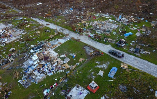 A road cuts through the rubble of homes that belong to the same family, destroyed by Hurricane Dorian in Rocky Creek East End, Grand Bahama, Bahamas, Sunday, Sept. 8, 2019. Bahamians are searching the rubble, salvaging the few heirlooms left intact by the Category 5 storm. (AP Photo/Ramon Espinosa)