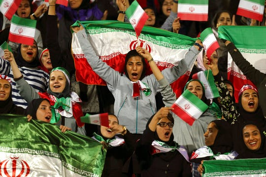 In this Oct. 16, 2018 file photo, Iranian women cheer as they wave their country's flag after authorities in a rare move allowed a select group of women into Azadi stadium to watch a soccer match in Tehran, Iran. Sahar Khodayari, an Iranian female soccer fan died after setting herself on fire outside a court after learning she may have to serve a six-month sentence for trying to enter a soccer stadium where women are banned, a semi-official news agency reported Tuesday, Sept. 10, 2019.