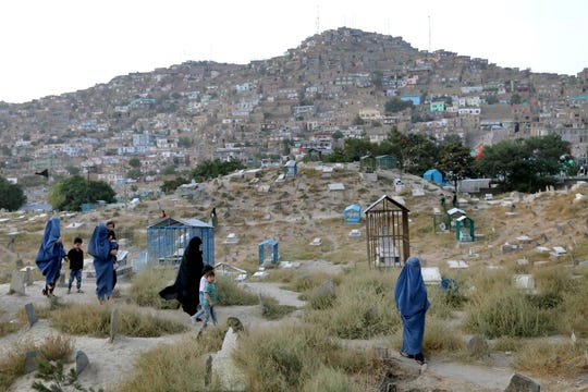 Women walk in the Karte Sakhi Cemetery on the outskirts of Kabul, Afghanistan, Monday, Sept. 9, 2019.