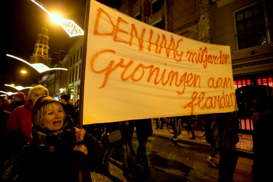 "A protester holds a banner reading ""The Hague Billions, Groningen To Shreds"" as thousands of people take to the streets in Groningen  to protest against gas extraction and related earthquakes."