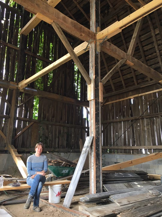 """Secret Sky"" designer Catie Newell, eating under the re-engineered beam work that now supports the barn."