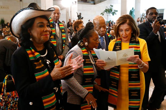 House Speaker Nancy Pelosi of Calif., right, reads a program with Rep. John Lewis, D-Ga., second from right, Rep. Sheila Jackson Lee, D-Texas, second from left, and Rep. Frederica Wilson, D-Fla., during a ceremony to commemorate the 400th anniversary of the first recorded arrival of enslaved African people in America, Tuesday, Sept. 10, 2019, on Capitol Hill in Washington.