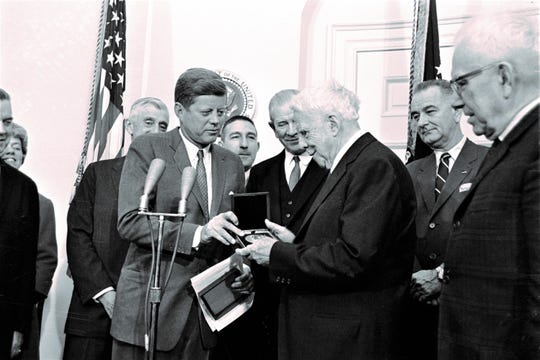 """Poet Robert Frost looks at the congressional medal after it was presented to him March 26, 1962, by President John F. Kennedy at a White House ceremony.  The award was for his contribution to American letters.  The white haired poet, who was celebrating his 88th birthday, remarked, """"This is a great, great, great thing.""""  In the background, from left, are Sen. Leverett Saltonstall, R-MA; Interior Secretary Stewart Udall; Sen. A. Willis Robertson, D-Vl; and Vice President Lyndon Johnson.  (AP Photo)."""