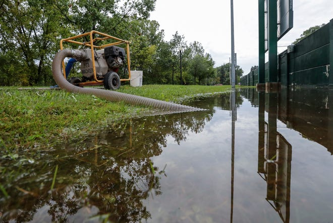 Water is pumped off the grass along the East River Trail after heavy rains Tuesday, September 10, 2019, at Joannes Park in Green Bay, Wis.