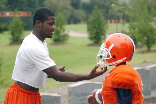 Clemson cornerback Ray Ray McElrathbey, left, adjusts the chin strap for his younger brother, Fahmarr, while the two play following football practice Tuesday, Sept. 5, 2006, in Clemson, S.C.