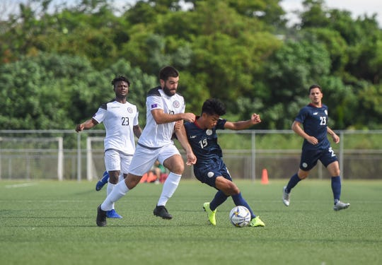 Team Guam's Mike Crowley battles for possession against Philippines midfielder Yrick Gallantes (19) during their Preliminary Joint Qualification Round 2 match for the FIFA World Cup Qatar 2022 and AFC Asian Cup China 2023 at the Guam Football Association National Training Center in Dededo Sept. 10, 2019.