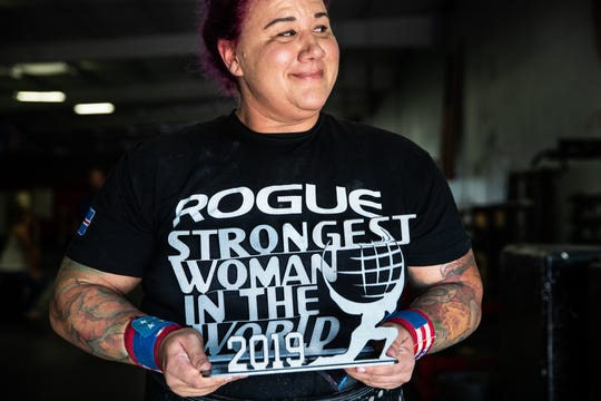 Jessica Fithen, who recently competed in Alaska to gain the title of Strongest Woman in the World, poses with her trophy at her gym, Unbreakable Athletics, in Plainfield, Ind., on Tuesday, Sept. 10, 2019. The competition, held in Palmer, Alaska, events included a dogsled drag, keg pressing, a 460 pound axle bar deadlift for reps, a keg relay load and a 55 pound salmon toss.