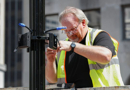 Garry Robbins, from Dodd Technology, installs CAT5 cables for the light and speakers on light poles around Monument Circle. Crews from Dodd Technologies work to install lights, speakers and projectors on and around Monument Circle on Tuesday, Sept. 10, 2019.