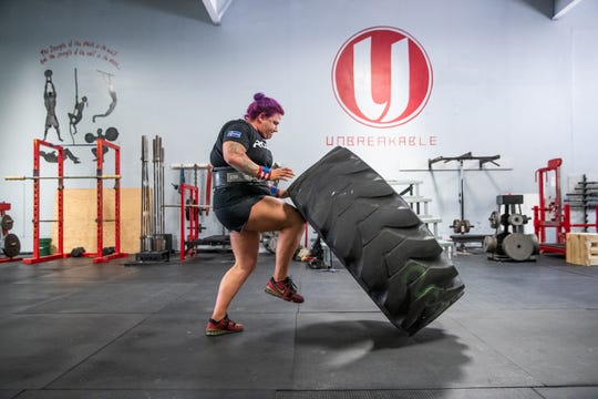 Jessica Fithen flips a tire at her gym, Unbreakable Athletics, in Plainfield, Ind., on Tuesday, Sept. 10, 2019. Fithen holds the title of Strongest Woman in the World.