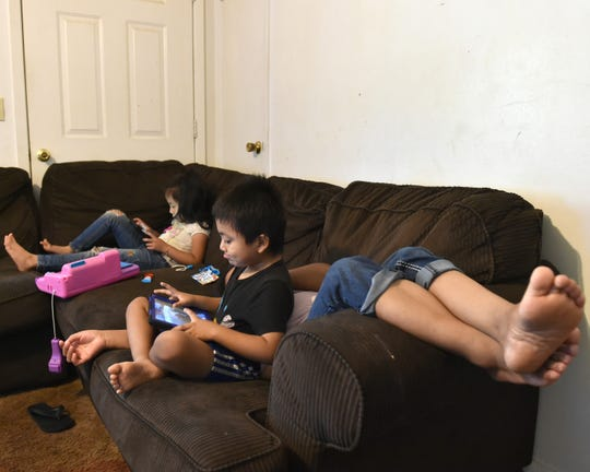 Siblings play games on their couch in the living room of their Carthage, Mississippi home on Wednesday, Sept. 4, 2019 as their exhausted mother rests after being released from immigration detention on a $3,000 bond. While she was locked up for three weeks, her husband E. Miranda had to stop working to take care of their three children.