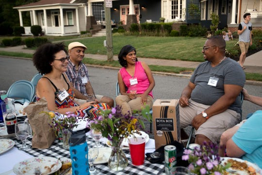 From left, Sherley Cruz, Elias Fernandez, Nina Martyris and Jerome Robinson during after-dinner socializing at the Historic Fourth and Gill Neighborhood Organization's long table potluck on Luttrell Street on Sunday, Sept. 8, 2019.