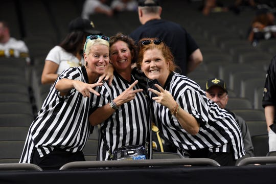 New Orleans Saints fans dressed as referees pose before an NFL football game against the Houston Texans in New Orleans, Monday, Sept. 9, 2019.