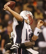 New England Patriots quarterback Tom Brady (12) is tackled by New Orleans Saints Anthony Hargrove during the second quarter of an NFL football game, Monday, Nov. 30, 2009, in New Orleans.