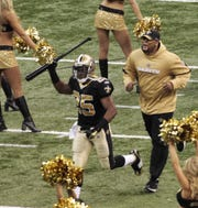 New Orleans Saints running back Reggie Bush (25) runs out onto the field carrying a baseball bat before the NFL football divisional playoff game against the Arizona Cardinals in New Orleans, Saturday, Jan. 16, 2010.