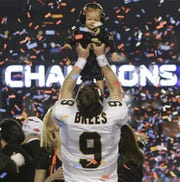 New Orleans Saints quarterback Drew Brees (9) holds his son Baylen after the NFL Super Bowl XLIV football game against the Indianapolis Colts in Miami, Sunday, Feb. 7, 2010. The Saints won 31-17.