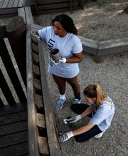 Fisher Catholic High School juniors Victoria Johnson, left, and Kaleigh Golden, right, paint part of the wooden playground Tuesday morning, Sept. 10, 2019, at Connexion West in Lancaster. Hundreds of volunteers fanned out across the county to work on volunteer projects as part of United Way of Fairfiled County's Community Care Day.