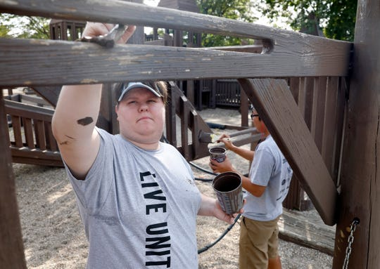 Fisher Catholic High School seniors Nick Henry, left, and Reagan Fagrell, right, paint part of the wooden playground Tuesday morning, Sept. 10, 2019, at Connexion West in Lancaster. Hundreds of volunteers fanned out across the county to work on volunteer projects as part of United Way of Fairfield County's Community Care Day.