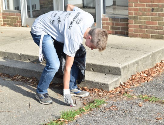 Aiden Jackson, a Fisher Catholic High School junior, picks up trash at Connexion West during the United Way of Fairfield County's Community Care Day.