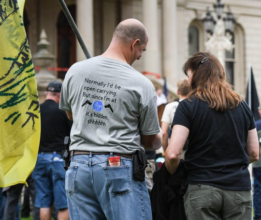 """Joel Gardner of Lansing shows his disdain for businesses that have recently asked customers not to open carry in their place of business, during the Second Amendment March at the Capitol Tuesday, Sept. 10, 2019.  """"They are slowly chipping away at our rights,"""" he said.   Also  pictured is Kelly VanRyckeghem of Dryden,"""