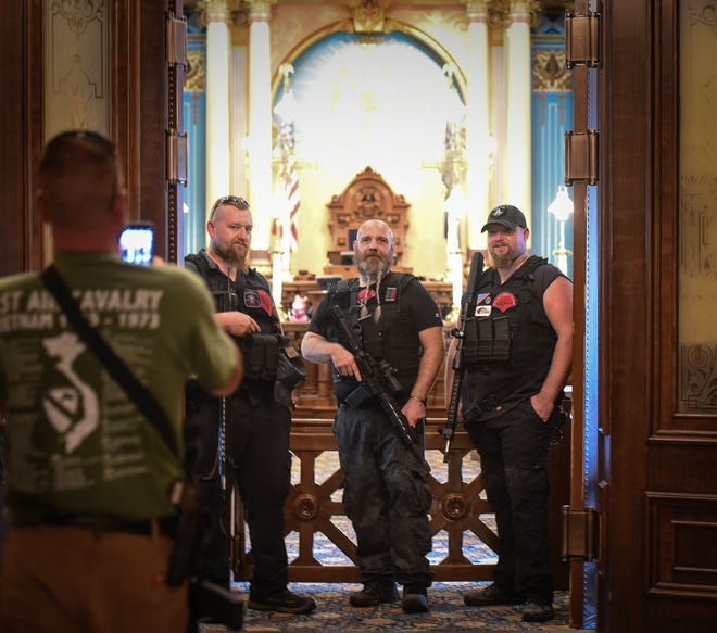 From left.  Ben Singer of the Michigan Liberty Militia takes a picture of fellow members outside senate chambers while touring the State Capitol after the Michigan Second Amendment March Tuesday, Sept. 10. 2019.