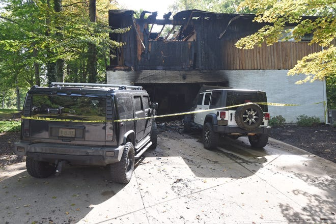 Two SUVs were damaged in the driveway of a home that caught fire at 161 Redwood Road in Mansfield early Tuesday morning.