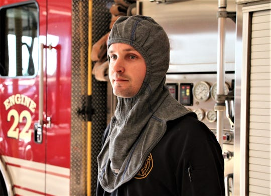 Firefighter Andrew Niles from the Marion Fire Department displays one of the new particulate-blocking hoods the department has purchased. A community fundraising campaign generated about $15,000 for the department to pay for the hoods, which officials say block 99 percent of contaminants from reaching firefighters' skin.