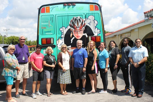 YMCA of South Collier personnel stand with sponsor Matt Walthour (blue shirt, center) after showing him the revamped vehicle at his Island Bike Shop.
