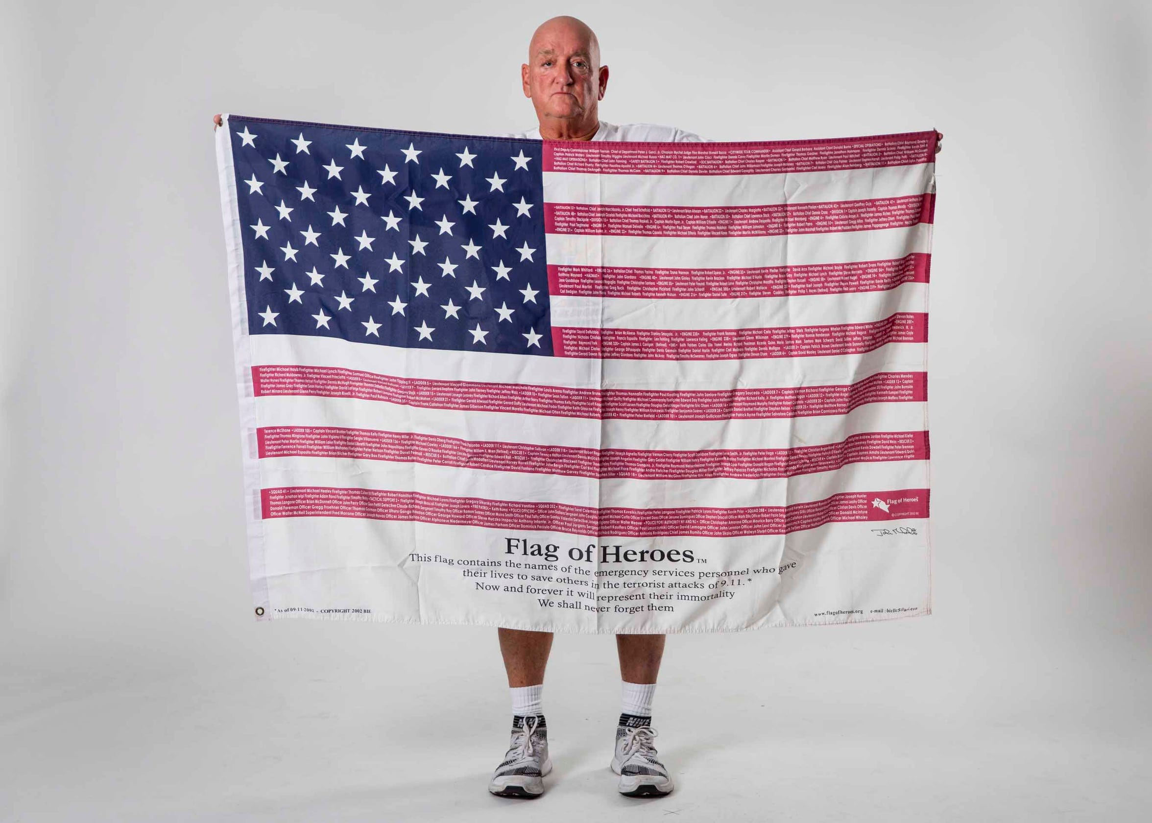 John Wholihan holds up a flag on Monday, Sept. 9, 2019, with the names of the emergency service personnel who lost their lives in service to others during the 9/11 terrorist attacks. The list of names on the flag was current as of 2002 but has continued to grow as hundreds of first responders have died of health complications related to exposure to toxic chemicals on 9/11.