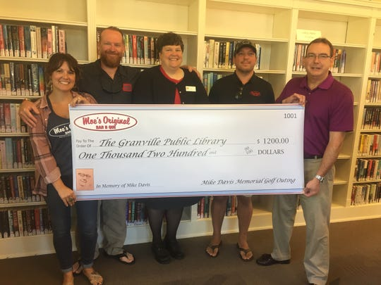From left: Moe BBQ's Kara Gallagher and Greg Tracey, Granville Public Library Director Anita Carroll, Justin Palm of Moe's, and Daniel Lavely during a recent check presentation at the library.