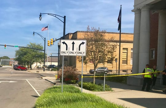 A suspicious package, seen on the far sidewalk near the traffic signal pole, has forced police to close the intersection of First and Main streets in downtown Newark.