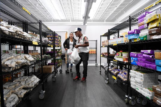 Francisco Miliano of Passaic, right, shops in the CUMAC food pantry with the help of Luisa Monroy on Tuesday, Sept. 10, 2019, in Paterson.