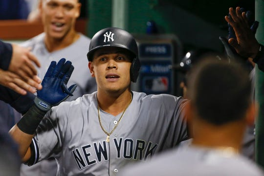 New York Yankees third baseman Gio Urshela (29) is welcomed back to the dugout after hitting a solo home run during the seventh inning against the Boston Red Sox at Fenway Park.