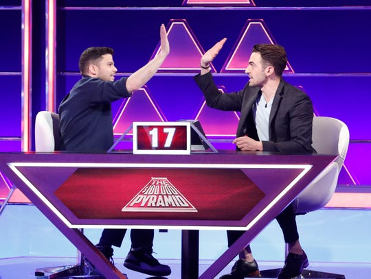 """Michael Reddin, at right, celebrates with his celebrity partner Jerry Ferrara on """"The $100,000 Pyramid."""""""