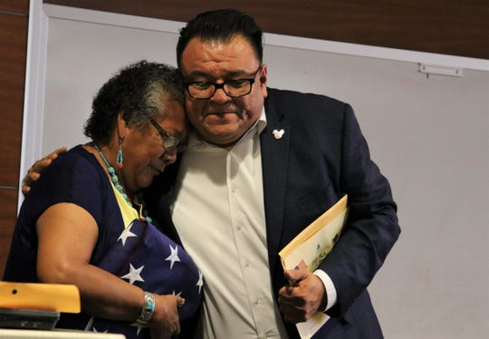 Flora Dennison accepts a flag from Brian Lee, a field representative for U.S. Rep. Ben Ray Lujan, D-NM. The flag flew over the capital in memory of Dennison's father, state Sen. John Pinto, D-Gallup.