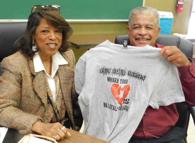 St. Landry Parish School Board members Joyce Haynes (left) and Raymond Cassimere hold up a shirt promoting the shop local campaign announced by district school officials.