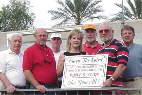 In this photo from an April 29, 2002 online newsletter from College of the Desert, a small group of supporters and Rotary Club members gathered and took turns mounting a memorial sign on a door leading to the football field under the stadium. The Palm Desert Palms-to-Pines Rotary Club spearheaded the memorial program, which includes scholarships to the high schools attended by Daniel Suhr and James Gray,  New York City firemen who died heroically in the Twin Towers explosion on Sept. 11. From left: John Marzicola, former COD instructor; COD athletic trainer Dave Anderson; athletic director John Marman; rotarian Cindy Farrell; rotarian and COD softball coach Shel Wellins; COD counselor Matteo Monica; and COD counselor Ken LaMont.