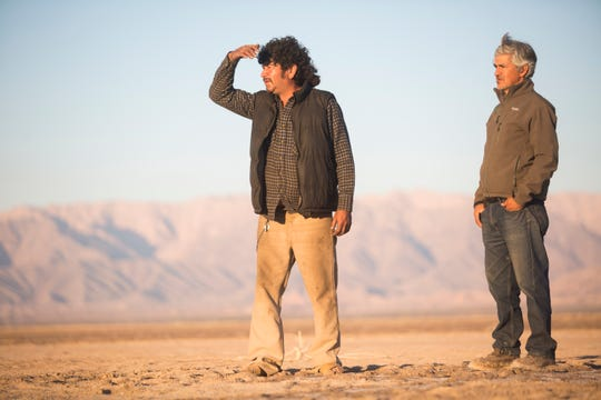 Jesús Antonio Muñoz and Arturo Guerrero Cortés stand in Laguna Salada, a dry lakebed in Baja California where locals claim to have seen a buried ship.