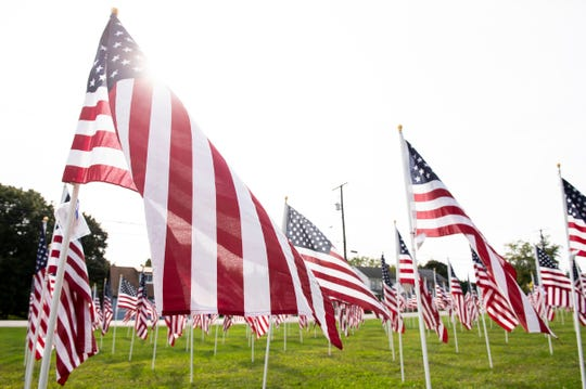 American flags blow in the wind at the  9/11 Memorial Healing Field at West Manheim Elementary School. Organized by the Exchange Club of Hanover, volunteers put up around 500 flags this year.